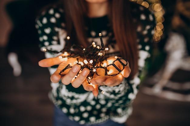 Junge frau durch den weihnachtsbaum mit weihnachtsglühenden lichtern