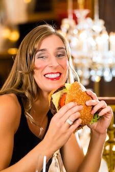 Junge frau, ein gourmetrestaurant, isst einen hamburger, sie verhält sich unkorrekt