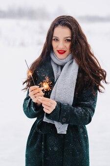 Junge frau eislaufen im freien auf einem teich an einem eiskalten wintertag mit wunderkerzen in der hand