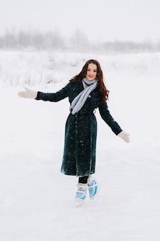 Junge frau eislaufen im freien auf einem teich an einem eiskalten wintertag