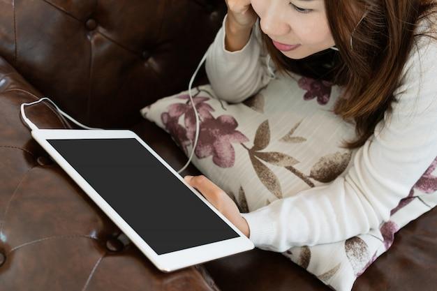Junge frau entspannt sich auf bequemer couch und benutzt tablette zu hause.