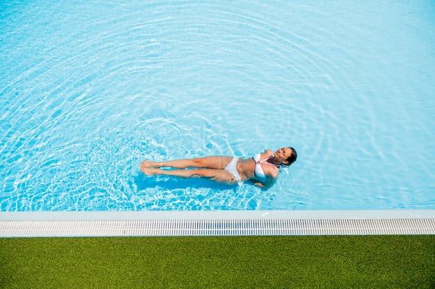 Junge frau entspannt sich im pool