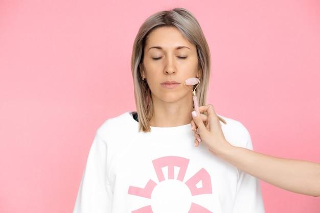 Junge frau erhält gouache-massage auf rosa hintergrund, studioaufnahme, helfende hand im spa, stock-foto