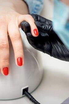 Junge frau erhält roten nagellack vom professionellen maniküremeister im nagelstudio