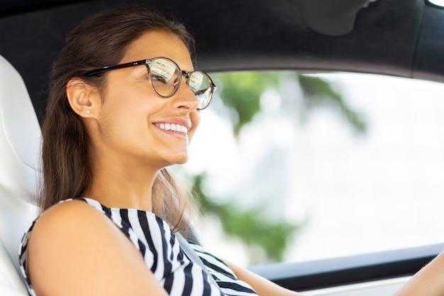Junge frau fährt. ansprechende junge frau mit gestreifter bluse, die beim autofahren lächelt