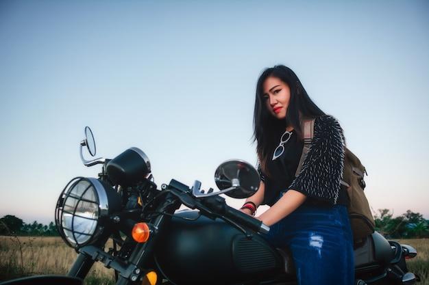 Junge frau fährt mit dem motorrad auf die straße und genießt die freiheit und den aktiven lebensstil.