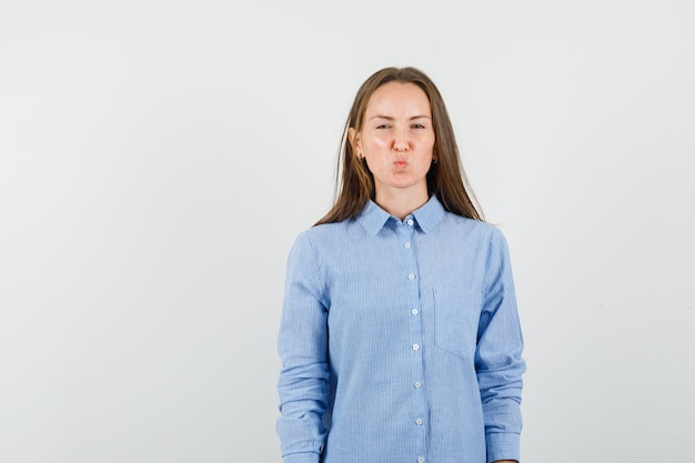 Junge frau finster, während lippen in blauem hemd gefaltet und beleidigt aussehen.