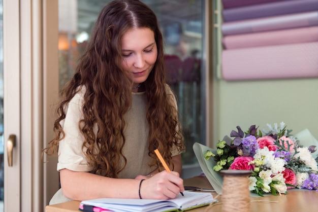 Junge frau floristin nimmt eine bestellung für einen blumenstrauß blumenladen arbeitsplatz lebensstil