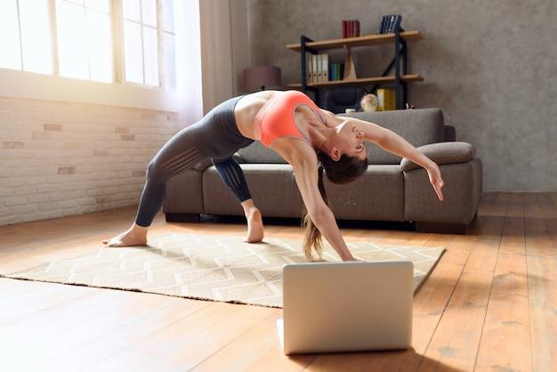 Junge frau folgt mit einem laptop einem fitnessstudio übungen. sie ist wegen der quarantäne von coronavirus codiv-19 zu hause