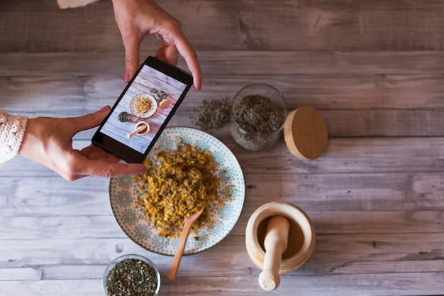 Junge frau food blogger macht foto für blog, bild eines holzmörsers, schüssel mit gelber kurkuma, lavendel und gesunden natürlichen zutaten. selektiver fokus, nahaufnahme. tagsüber