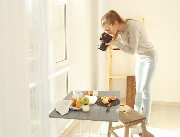 Junge frau fotografiert essen im haus