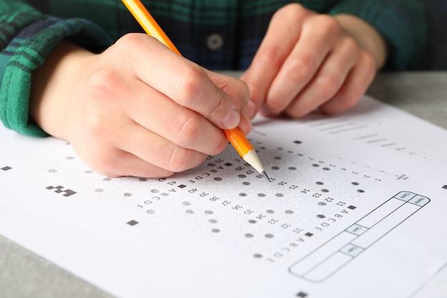 Junge frau füllt testblatt auf grauem tisch, nahaufnahme