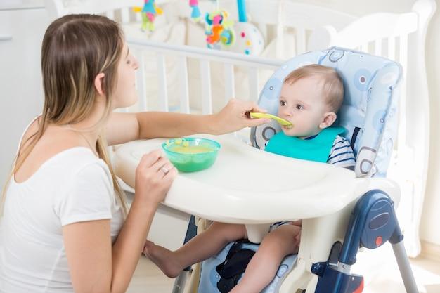 Junge frau füttert ihr baby vom löffel mit apfelmus