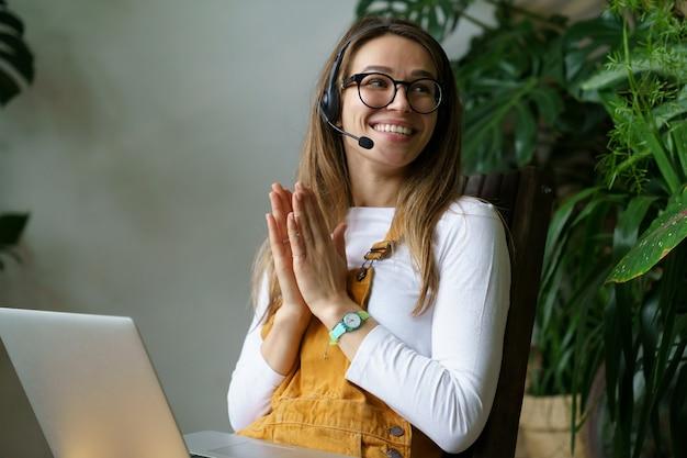 Junge frau gärtnerin kleinunternehmer sprechen über videoanruf mit kunden oder partner mit laptop