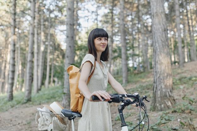 Junge frau gegen naturhintergrund mit fahrrad