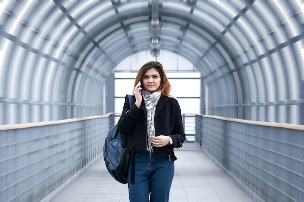 Junge frau geht schnell eine überdachte fußgängerüberführung entlang, telefoniert und lächelt