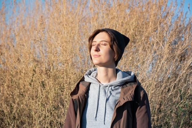 Junge frau genießt die herbstsonne. frau im parka draußen am hellen sonnigen nachmittag