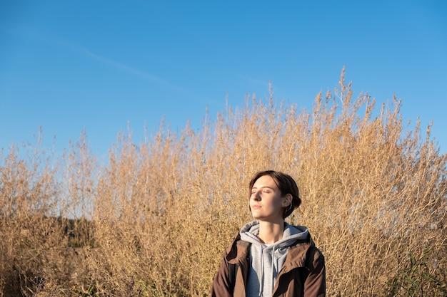 Junge frau genießt die herbstsonne. frau im parka draußen in einer wiese am hellen sonnigen nachmittag