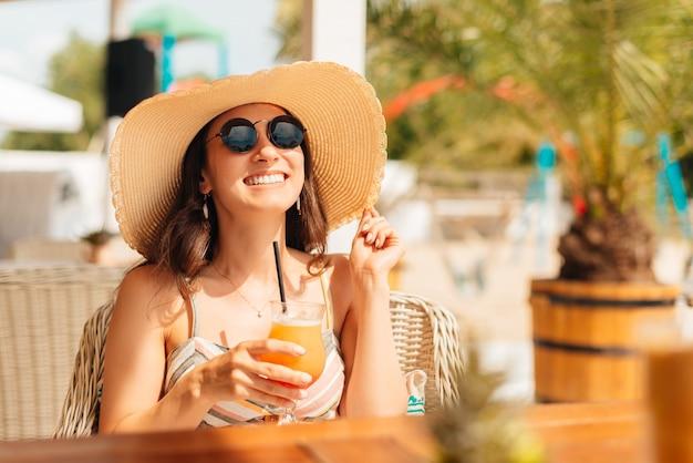 Junge frau genießt einen cocktail im freien am strand.