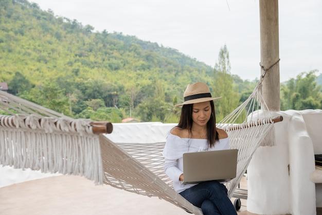 Junge frau genießt einen laptop in einer hängematte am strand