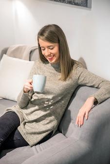 Junge frau genießt einen morgen tasse kaffee oder tee zu hause schließt ihre augen mit vergnügen, wie sie den geschmack schmeckt