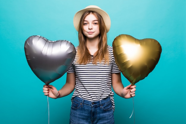 Junge frau genießt festlichen anlass, der metallische luftballons hält
