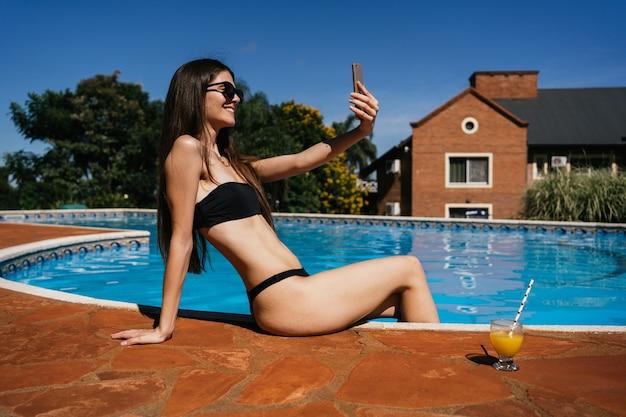 Junge frau genießt ihren urlaub, indem sie ein selfie am pool macht.