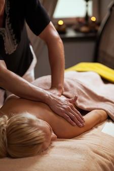 Junge frau genießt massage in einem badekurort