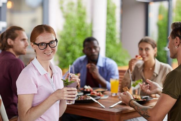 Junge frau genießt mittagessen mit freunden im cafe