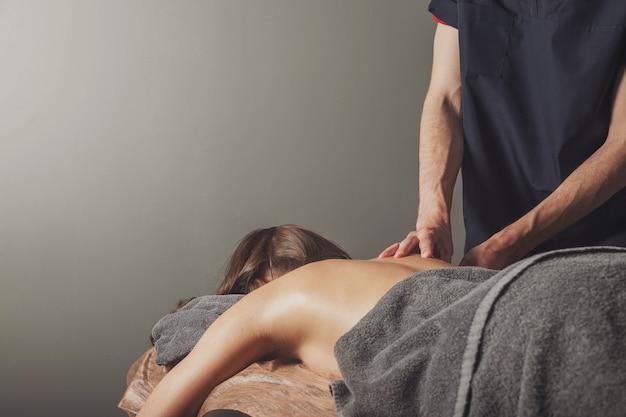 Junge frau genießt sport-wellness-massage in der arztpraxis des fitnessraums