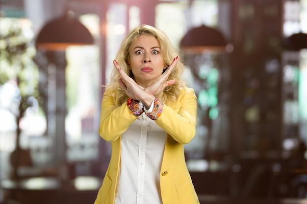 Junge frau gestikuliert stop mit den händen. wütende blonde frau in formeller kleidung gestikulierenden stopp kreuzte ihre hände.