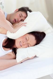 Junge frau gestört durch das schnarchen ihres freundes im schlafzimmer