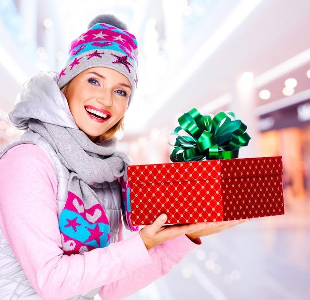 Junge frau gibt das weihnachtsgeschenk in einer winteroberbekleidung gekleidet - drinnen
