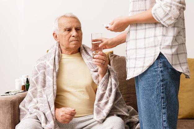 Junge frau gibt ihrem kranken älteren großvater zu hause medizin