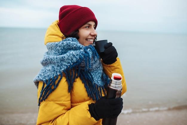 Junge frau gießt heißen tee aus einer thermoskanne in eine tasse und trinkt am meer. touristin trinkt am kalten winterstrand ein wamn-getränk. trampen, reisekonzept.