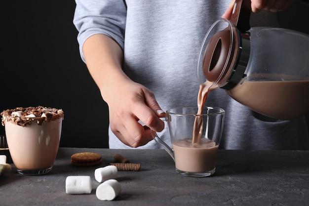 Junge frau gießt kakaogetränk in tasse auf schwarzem hintergrund, nahaufnahme