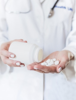 Junge frau gießt medizin, kapsel oder pille in ihre hand aus.