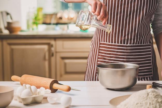 Junge frau gießt öl in eine schüssel mit teig, nahaufnahme. eine frau in gestreifter schürze kocht in der küche