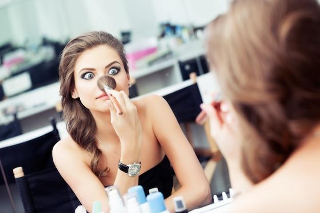 Junge frau grimassen und witze mit einem make-up-pinsel vor einem spiegel