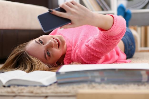 Junge frau haben eine pause auf dem boden liegen halten smartphone in den armen