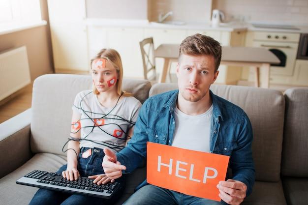 Junge frau haben social-media-sucht. auf dem sofa sitzen. mit schnur umwickelt. hände auf der tastatur. geisel von social media. emotionslose frau. besorgter mann hält hilfspapier.