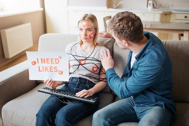 Junge frau haben social-media-sucht. emotionslos auf dem sofa sitzen. körper mit schnur umwickelt. hände auf der tastatur. junger mann berührt sie. frau halten papier, das ich mag.