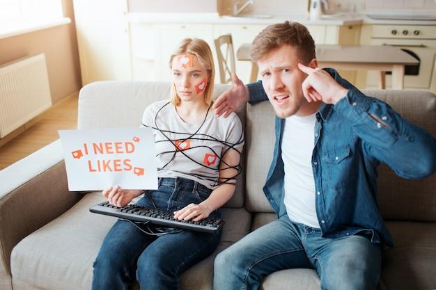 Junge frau haben social-media-sucht. emotionslos auf dem sofa sitzen. körper mit schnur umwickelt. hände auf der tastatur. papier halten brauche ich mag. verrückter junger mann schaut auf kamera und zeigt auf kopf.