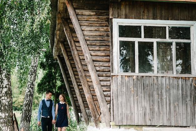 Junge frau hält ehemanns hand, die durch birke nahe einem alten hölzernen stilvollen haus geht