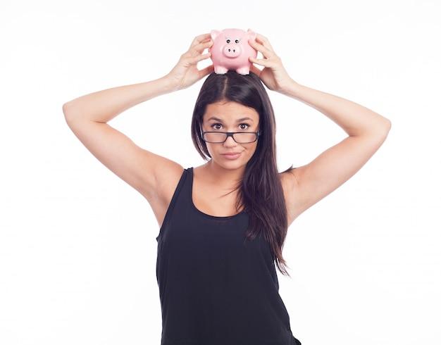 Junge frau hält ein sparschwein