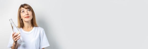 Junge frau hält eine flasche mit klarem wasser. banner. das konzept von durst, wärme, gesundheits- und schönheitspflege, wasserhaushalt