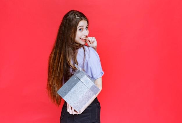 Junge frau hält eine silberne geschenkbox und versteckt sie hinter sich.