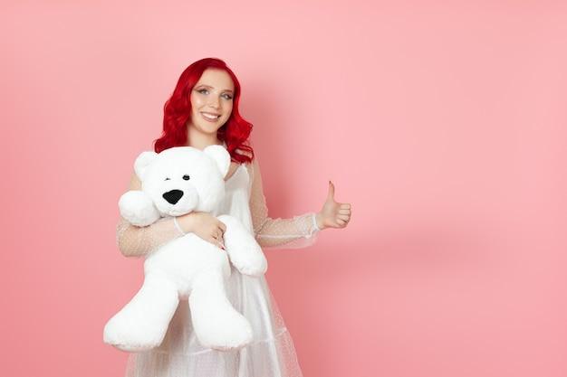 Junge frau hält einen großen weißen teddybär und gibt einen daumen hoch