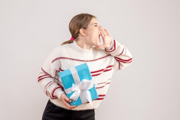 Junge frau hält geschenk und ruft laut jemanden auf weiß