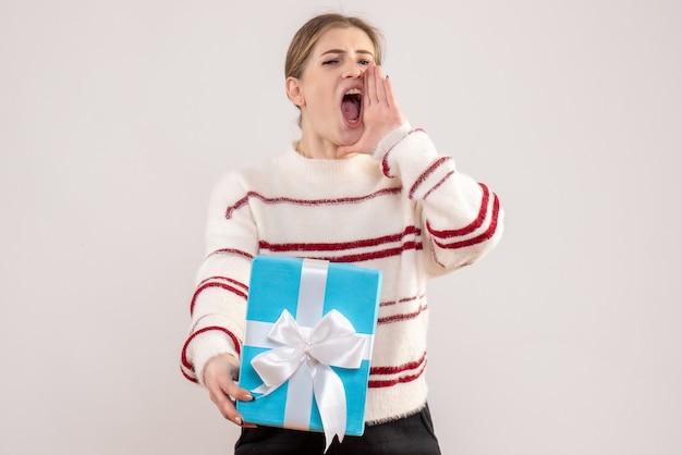 Junge frau hält geschenk und schreit auf weiß